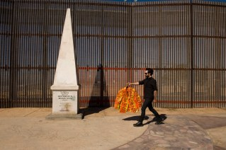 Artist Pablo Llana at the border fence in Playas de Tijuana, Mexico. The jacket is entirely made from Reese's king size peanut butter cup wrappers. Pablo Llana's art often depicts extreme and unhealthy food consumption in the industrial world. ..LA FRONTERA: Artists along the US Mexican Border.© Stefan Falke.http://www.stefanfalke.com/.