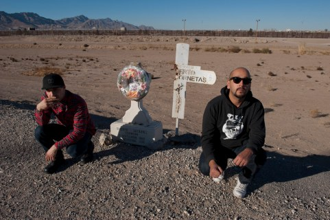 Hip Hop musicians Carlos Juan Avila Felix and Alejandro Neave of Sistemas Vocales in Ciudad Juarez, Mexico. The border fence between Juarez and El Paso in the distance. The crosses along the border are in memory of people who died trying to cross into the US, often swimming through the dangerous Rio Grande, which at this time of the year is completely dried out. Ciudad Juarez, Chihuahua, Mexico. This picture is part of my long-term project LA FRONTERA: Artists along the US Mexican Border. © Stefan Falke / www.stefanfalke.com