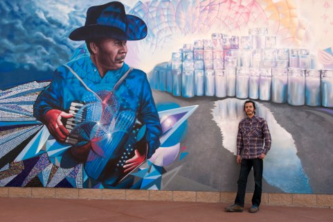 Muralist Werc Alvarez in front of his mural (90 feet long,11 feet tall) at the entrance to the Stanton Bridge which connects El Paso, USA, with Ciudad Juarez, Mexico.