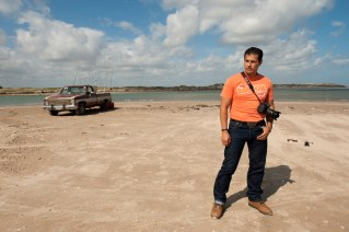 Photographer Eduardo Luzuriaga in Boca del Rio on the Atlantic coast at the border to the United States and Matamoros, Mexico. This is the very most North Eastern corner of Mexico. The middle of the Rio Grande marks the border. The river is very shallow here, people walk into it to fish. It is theoretically easy to cross into the US from here, but the US border control on the other side makes this almost impossible. Matamoros, Tamaulipas, Mexico. © Stefan Falke www.stefanfalke.com
